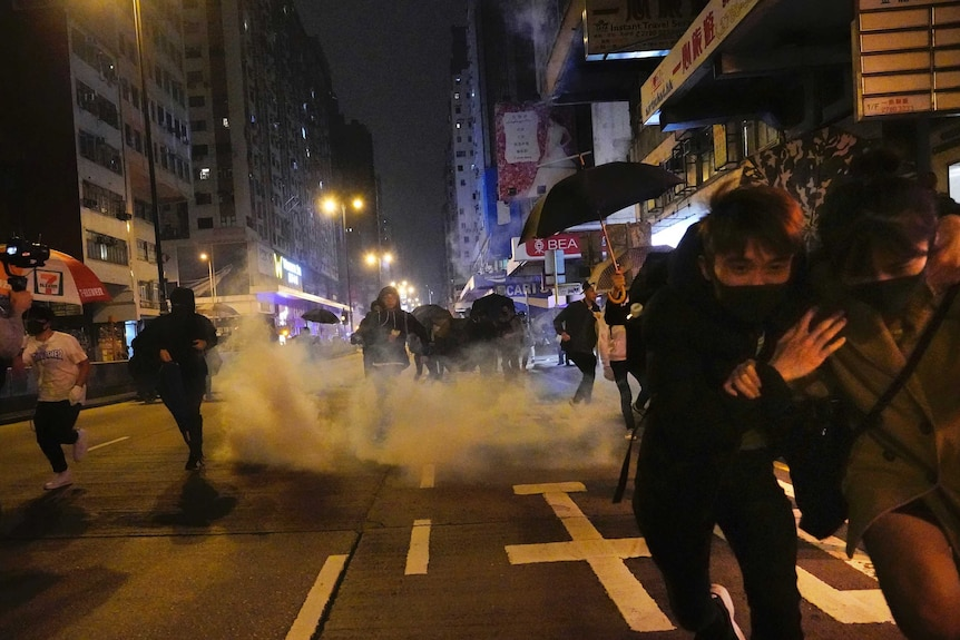 Protesters react as police fire tear gas during a demonstration in Hong Kong.