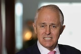 Malcolm Turnbull speaks to the media, holding his glasses in one hand and clenching his other first.