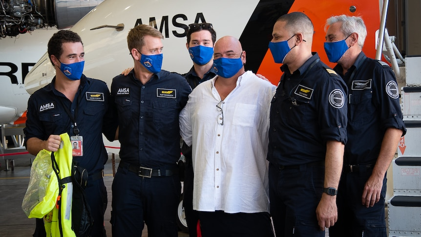 Man embraces AMSA officers in front of plane