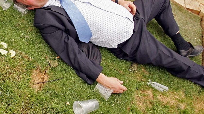 A male race-goer passes out after one too many drinks