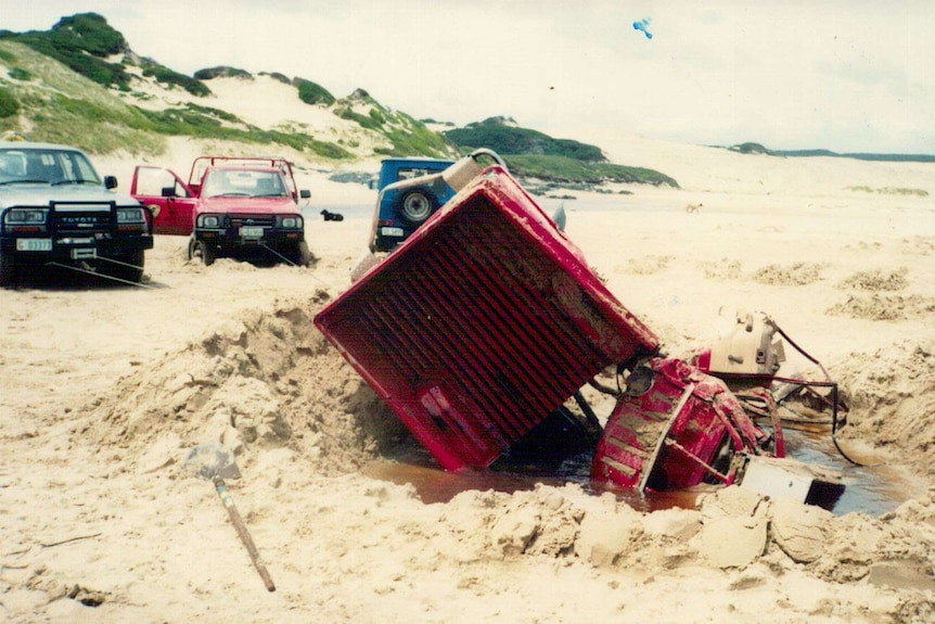 A red hilux ute that's been pulled to bits by other vehicles that have tried to winch it out of sand.