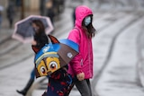 Many people wear face masks as they move along a shopping street as rain falls in Nottingham.