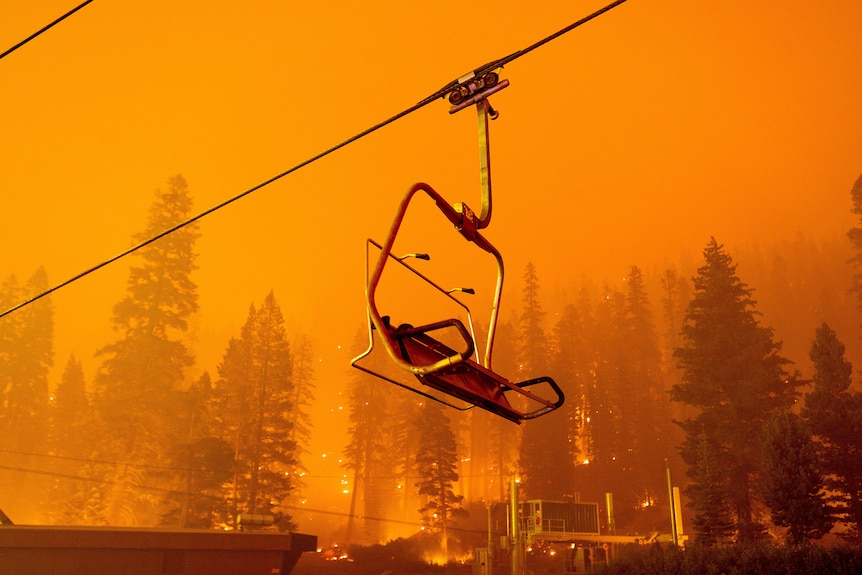 A chairlift dangles overhead as pine trees are engulfed by fire behind it.