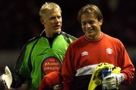 Two goalkeeping teammates have a laugh together at training.