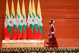 Myanmar State Counsellor Aung San Suu Kyi walks off the stage.