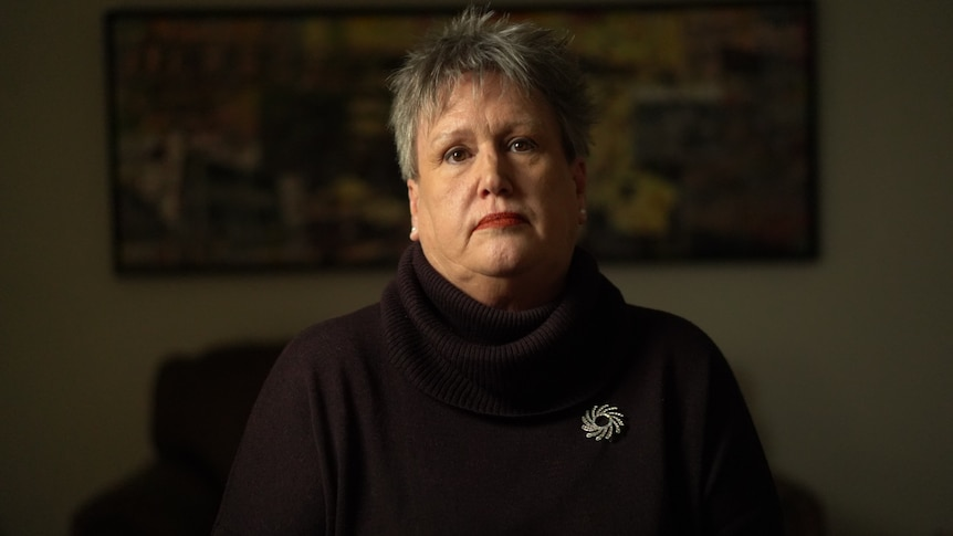 A woman with short hair wearing a dark-coloured turtle-neck.