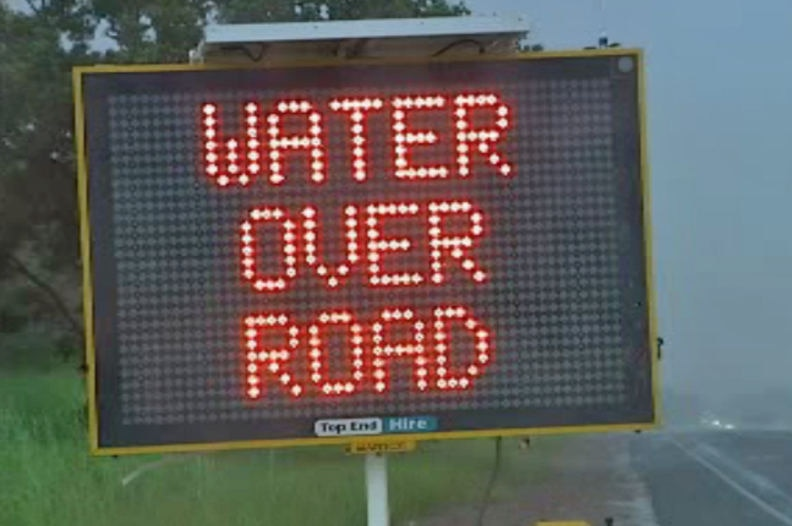 A digital road sign displays the message WATER OVER ROAD. It appears to be heavily raining