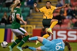 Sam Kerr passes the ball past the goal keeper who is diving at her feet