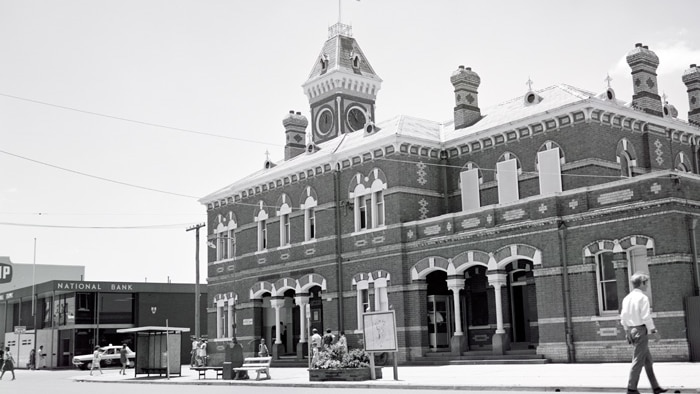 black and white image of bricked building with clock tower