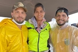 Dark haired woman stands in middle of two dark haired, bearded men, all wearing yellow jackets