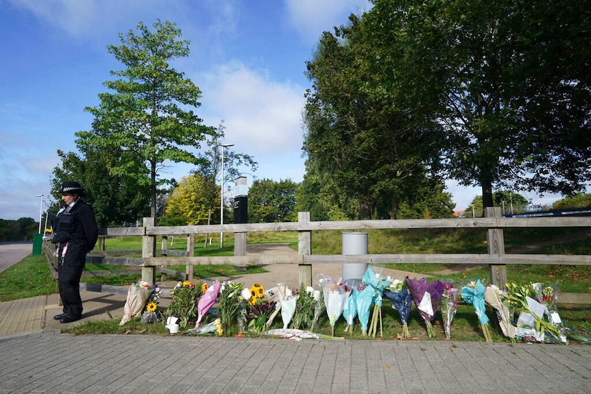 Flower tributes on a fence outside a park.