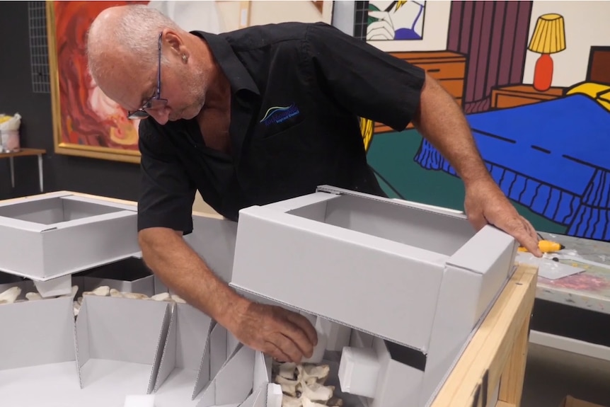 A man with spectacles and a black shirt places a box into a packing crate with colourful paintings behind him.