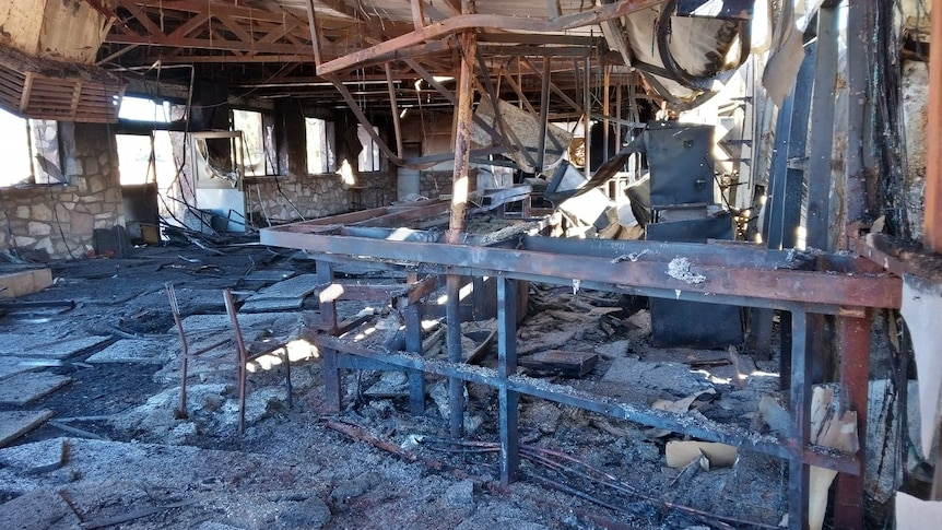 The blackened interior of a pub that has been destroyed by fire.