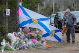 A older man pays his respects placing a teddy bear at a roadside memorial in Portapique.