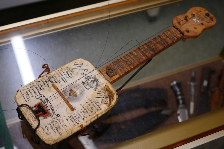 A wooden stringed instrument (banjo) inscribed with handwritten words.
