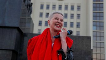 Belarusian opposition figure Maria Kolesnikova smiles as she holds a microphone.
