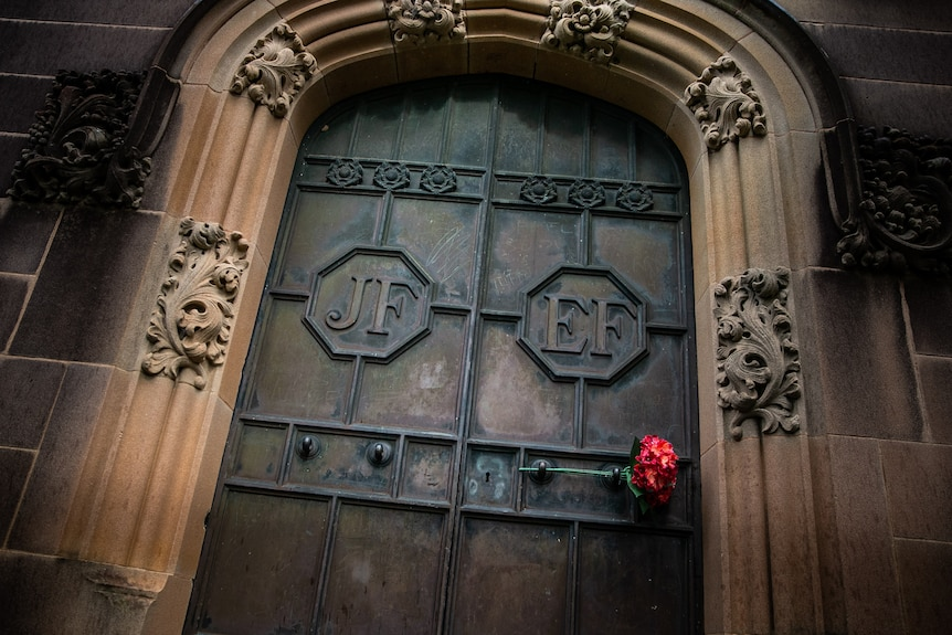 Heavy metal doors with the initials JF and EF and a rose threaded through.