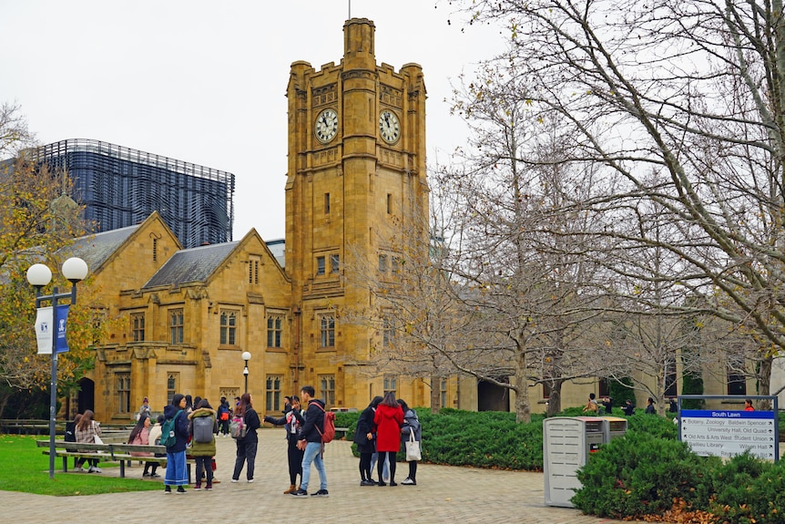 About a dozen student are seen talking in a courtyard, in front of a tall sandstone clock tower at the University of Melbourne.