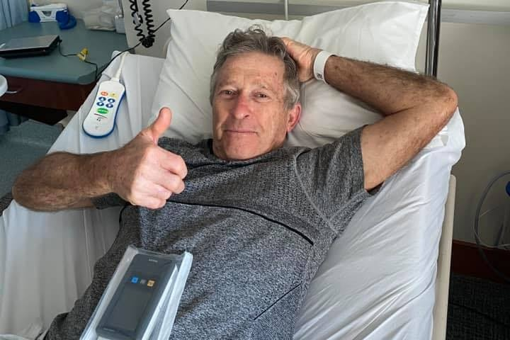 a man with a grey shirt lays in a hospital bed, giving a thumbs up towards the camera