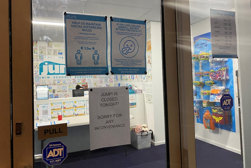 The window of a swim school with signs explaining that it's shut.