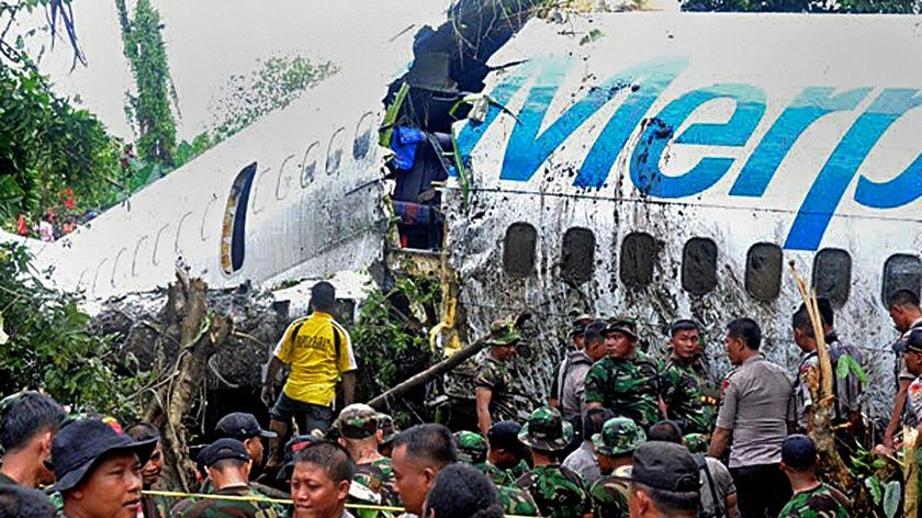 Indonesian soldiers and police examine the Merpati airline Boeing 737.