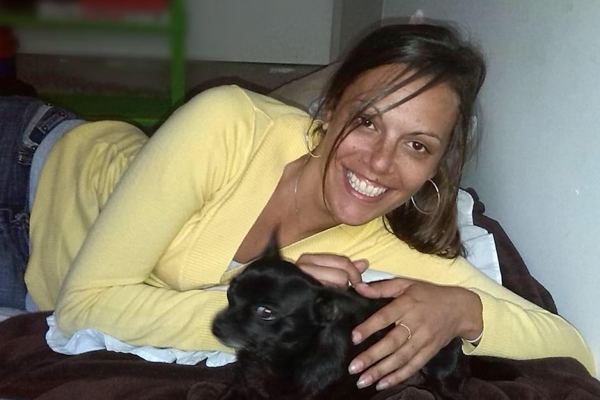 A smiling, bright-eyed woman with dark hair lying down and cuddling a pet.