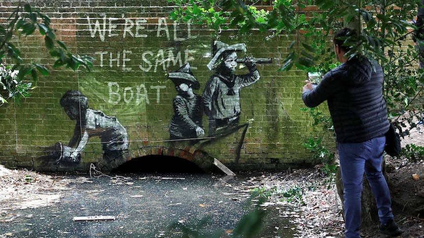 a person stands near a drain where a banksy article showing children in boat with the words we're all in the same boat above it