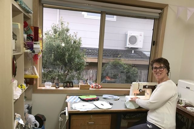 Tracey Nuthall sits at her desk by a window with a sewing machine, holding material and smiling at the camera.