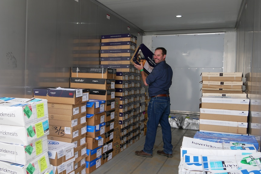 A man is holding a box, and is in a large freezer with stacks of boxes.