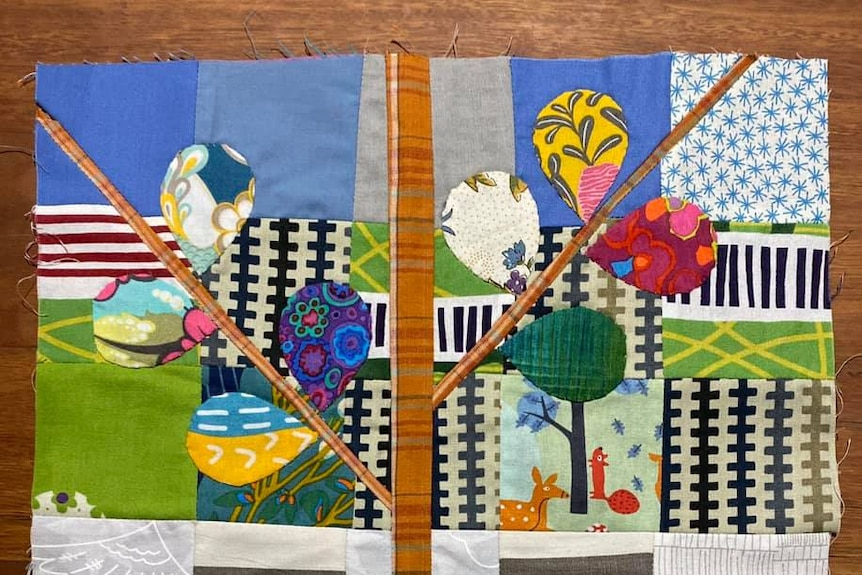 Four squares of fabric, two with colourful tree designs and patterns on a wooden table.