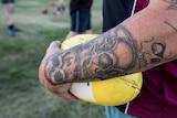 Tattooed arm holding Australian Rules football at team training, Tasmania.