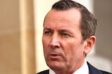 WA Premier Mark McGowan speaks at a media conference outside parliament, he wears a red tie and suit