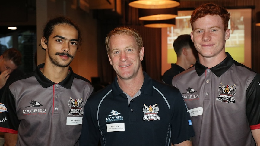 three men in similar shirts stand at a function