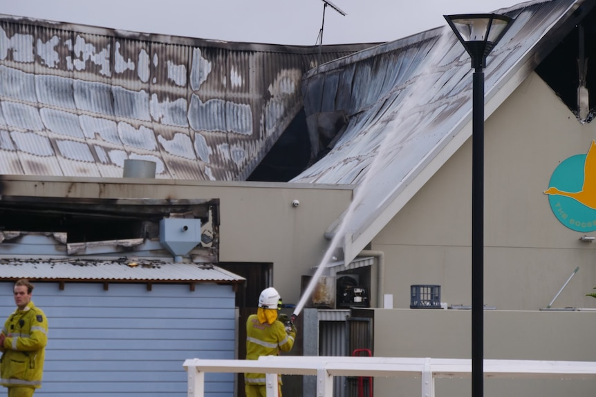 A firefighter squirting the roof of a restaurant with a visible hole in the top after a fire burnt through.