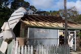 A tin roof hangs off the side of a house after being ripped off by strong winds.