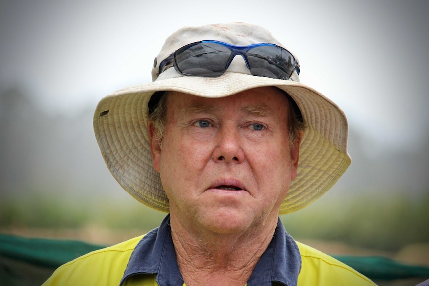 A middle-aged man in a work shirt and a white hat, with sunglasses sitting on the hat.