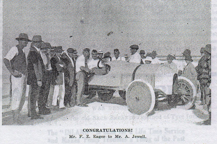 Historic photograph of race car on a beach surrounded by men wearing hats.