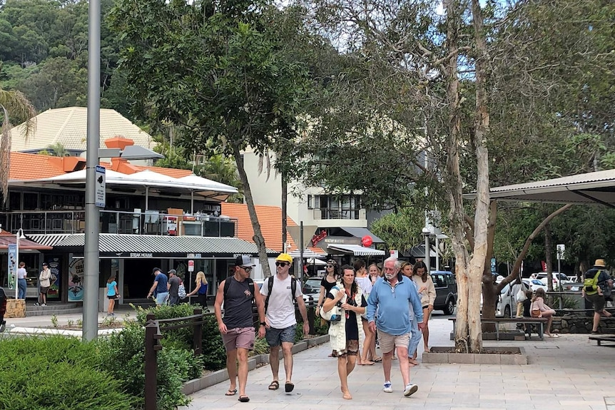 Groups of people walking past restaurants and cafes in a leafy street.