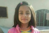 A young girl wearing a pink jacket and colourful shirt