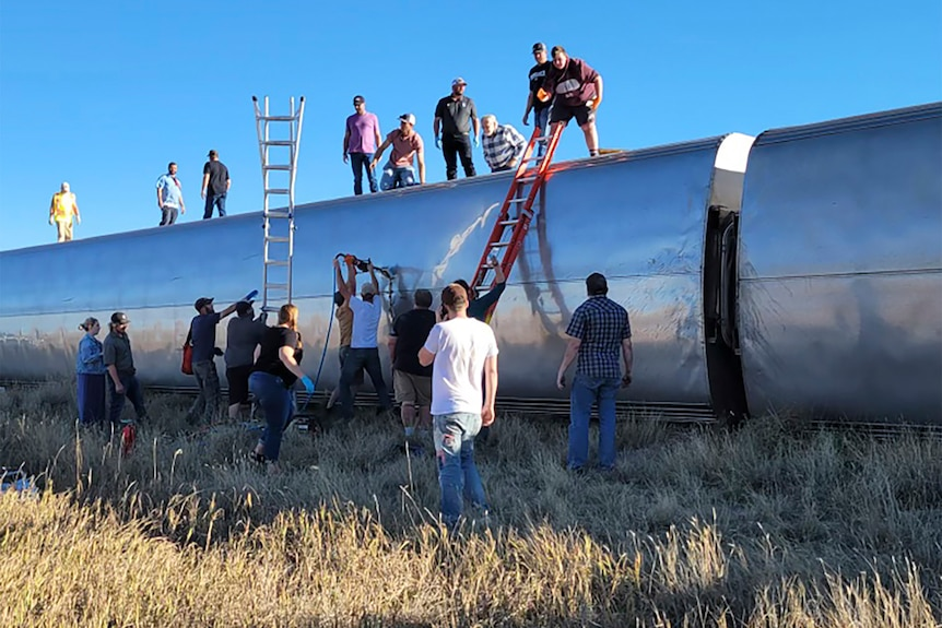 People work at the scene of the derailment, standing ladders against the derailed carriages and climbing on top.