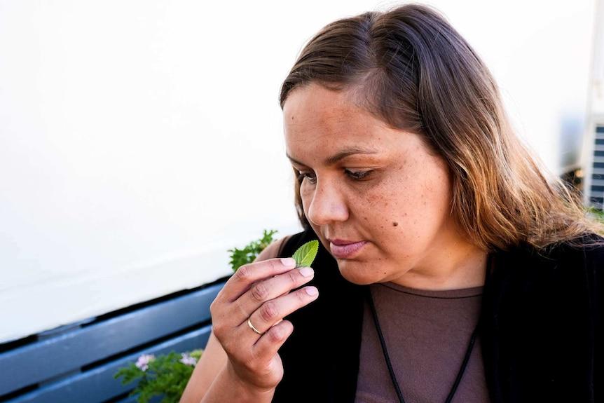 A woman smelling a chocolate mint leaf sitting down.