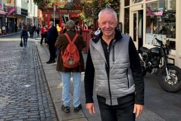 An elderly man stands in a cobble stone street and smiles to the camera.