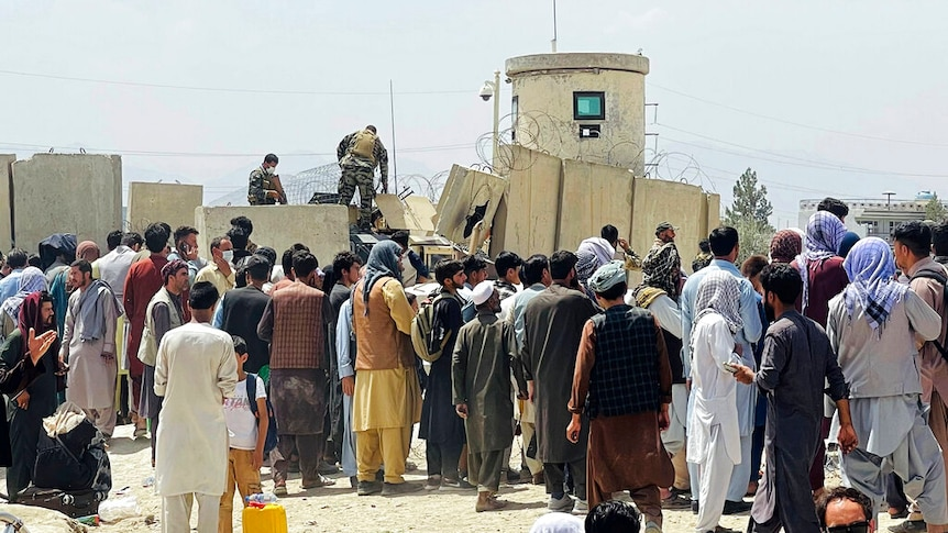 Afghan security guards stand on a wall as hundreds of people gather outside the international airport in Kabul.