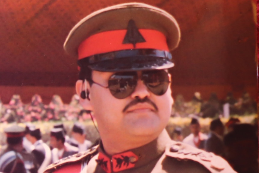 A Nepalese man with a moustache in a brown and red military uniform