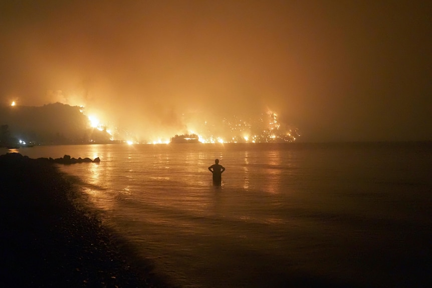 A man stands in water with flames in the distance