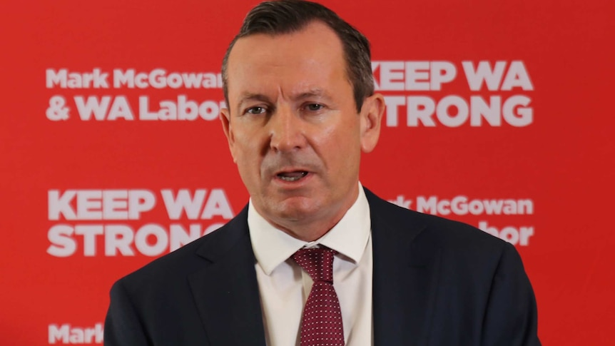 A head and shoulders shot of WA Premier Mark McGowan speaking at a media conference in front of a red Labor display.