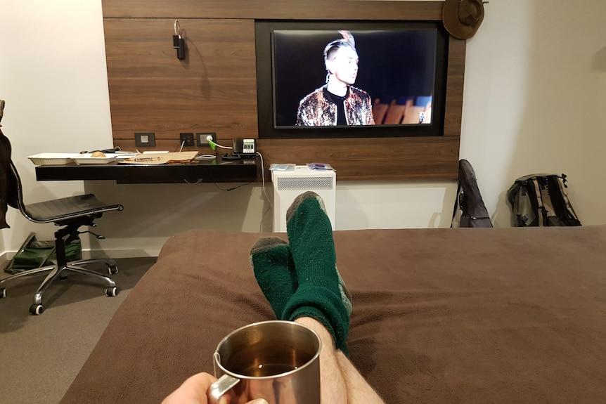 Feet up on bed, TV on in hotel room