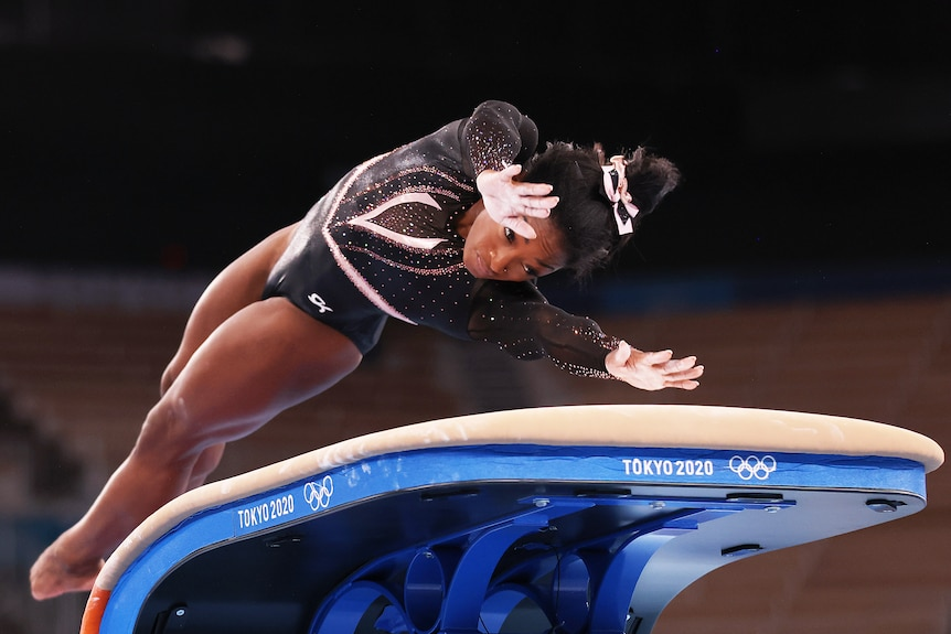 Simone Biles twists her body in mid-air as she reaches her hands out to plant on the vault in Olympic training.
