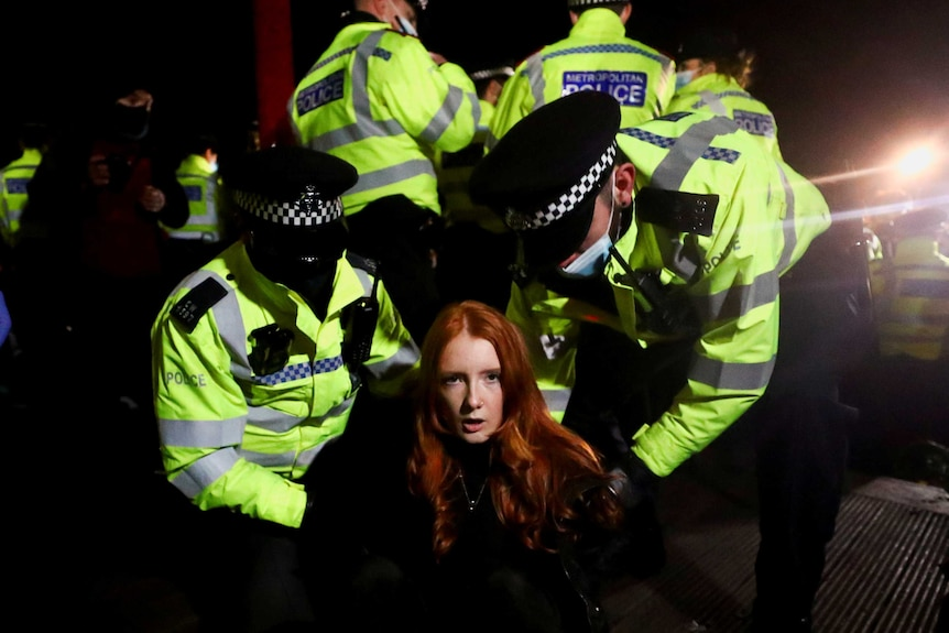 Police put handcuffs on a woman looking at the camera.