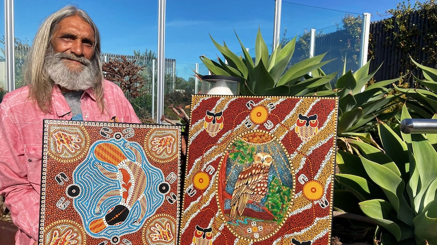 Stanley Geebung sits with two of his artworks outside in a garden.